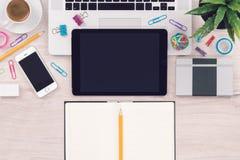 与膝上型计算机片剂智能手机和开放笔记薄的办公桌工作场所顶视图与铅笔 免版税库存图片