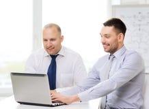 与膝上型计算机的两个微笑的商人在办公室 库存图片