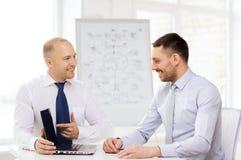 与膝上型计算机的两个微笑的商人在办公室 图库摄影