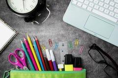 与膝上型计算机的五颜六色的学校用品 免版税库存照片