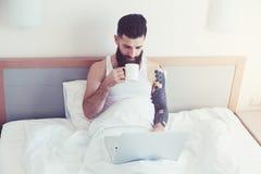 与膝上型计算机的人饮用的咖啡 库存图片