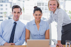与膝上型计算机的企业队微笑对照相机的 库存照片