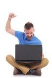 与膝上型计算机的供以座位的年轻偶然人欢呼 免版税图库摄影