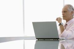 与膝上型计算机的周道的商人在会议桌上 免版税图库摄影