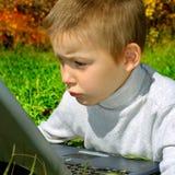 与膝上型计算机的哀伤的孩子 图库摄影