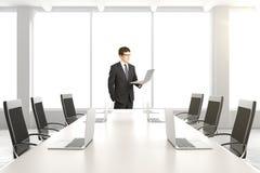 与膝上型计算机的商人在有选项的现代白色会议室 库存图片