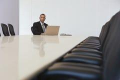 与膝上型计算机的商人在证券交易经纪人行情室 库存照片