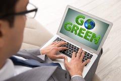 与膝上型计算机的商人在绿色环境概念 免版税库存照片