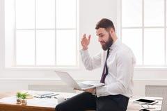 与膝上型计算机的困惑的商人在现代白色办公室 库存图片