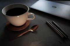 与膝上型计算机的在具体桌上的咖啡和笔 免版税库存照片