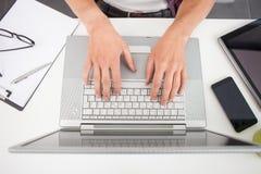 与膝上型计算机的坚硬运作的过程在桌上 库存照片