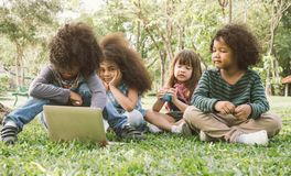与膝上型计算机的孩子在公园 库存照片