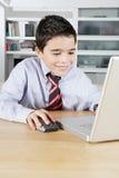 与膝上型计算机的孩子在家 免版税库存图片