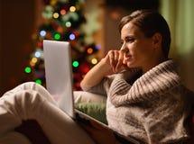 与膝上型计算机的少妇坐的椅子 免版税库存图片