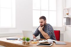 与膝上型计算机的年轻严肃的商人在现代白色办公室 库存照片