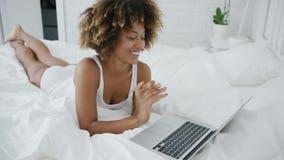 与膝上型计算机的年轻模型在床上 影视素材