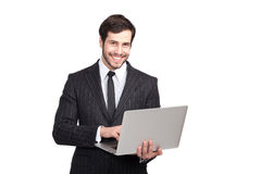 与膝上型计算机的微笑的商人 免版税库存图片