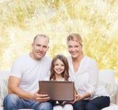 与膝上型计算机的微笑的家庭 图库摄影