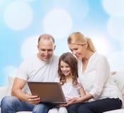 与膝上型计算机的微笑的家庭 免版税库存照片
