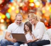与膝上型计算机的微笑的家庭 免版税库存图片