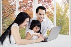 与膝上型计算机的快乐的家庭在家 免版税图库摄影