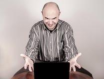 与膝上型计算机的恼怒和紧张的商人 图库摄影