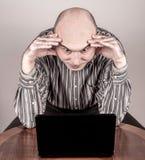 与膝上型计算机的恼怒和紧张的商人 库存图片