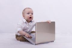 与膝上型计算机的惊奇的婴儿商人 使用与笔记本的逗人喜爱的小孩男孩 极端程度的想法惊奇 库存图片