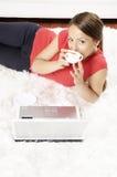 与膝上型计算机的愉快的妇女饮料咖啡 免版税库存图片