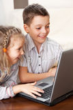 与膝上型计算机的愉快的孩子 免版税图库摄影