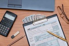 1040与膝上型计算机的报税表在桌上 库存照片