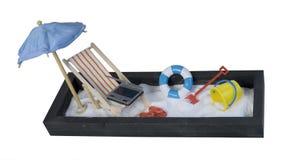 与膝上型计算机的海滩睡椅和伞和沙子 库存照片