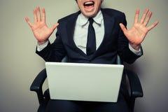 与膝上型计算机的激动的年轻商人 库存照片