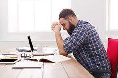 与膝上型计算机的疲乏,劳累过度的商人在现代白色办公室 库存图片
