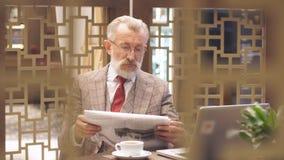 与膝上型计算机的老商人在他的办公室概念的咖啡休息 影视素材