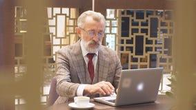 与膝上型计算机的老商人在他的办公室概念的咖啡休息 股票录像
