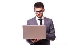 与膝上型计算机的年轻商人被隔绝在白色背景 免版税库存照片