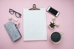 与膝上型计算机纸笔记本电话,板料,铅笔,糖果,咖啡,耳机,植物的自由职业者的概念在桃红色背景书写 库存照片