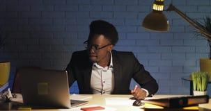 与膝上型计算机跳舞的年轻愉快和滑稽的商人由书桌在夜间的办公室 工作狂,最后期限概念 股票视频