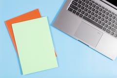 与膝上型计算机键盘和五颜六色的笔记本的工作区在蓝色背景 免版税库存照片