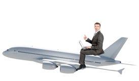 与膝上型计算机飞行的商人在喷气机 免版税库存图片