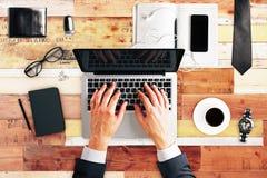 与膝上型计算机,咖啡的键入的商人,空白的日志盖子 免版税库存图片