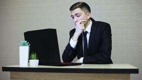与膝上型计算机,由桌的疲乏的开会的年轻商人在办公室 股票录像