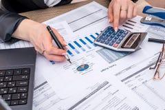 与膝上型计算机,笔的女商人帐户年度预算 免版税库存照片