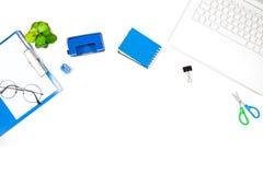 与膝上型计算机,笔记本,打孔器,剪贴板的办公桌桌 库存照片