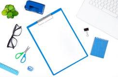 与膝上型计算机,笔记本,打孔器,剪贴板的办公桌桌 图库摄影