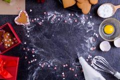 与自创曲奇饼框架的黑石背景在心脏、花、食品成分和装饰形状的  恋人的礼物Val的 图库摄影