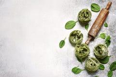 与自创菠菜面团tagliatelle的食物背景,木 免版税图库摄影