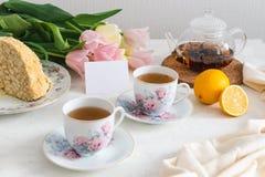 与自创蛋糕、柠檬、茶壶和郁金香的茶会在背景 复制空间 库存照片