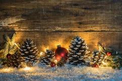 与自然杉木锥体、红色球、冷杉分支和光的冷漠的圣诞节背景在雪在晚上 免版税库存照片